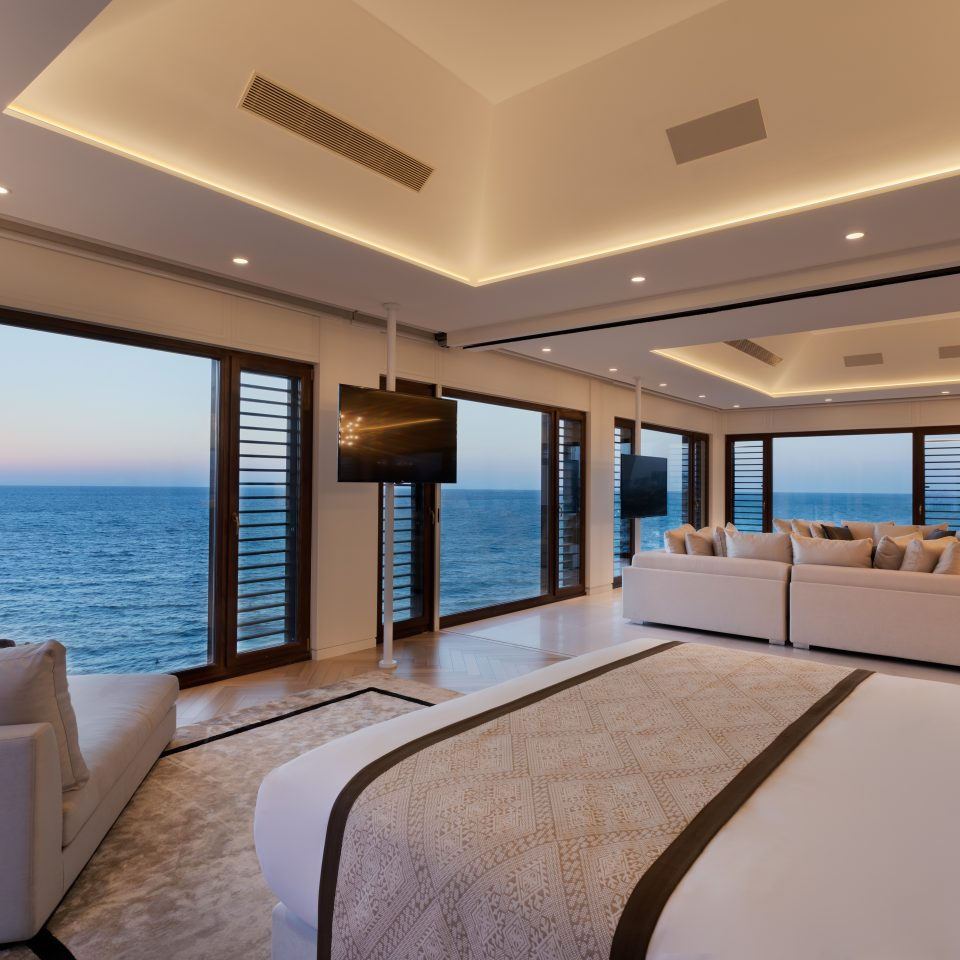 presidential suite with ocean views from numerous large windows at dusk