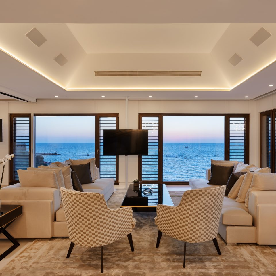 presidential suite living space with two couches and two chairs facing large windows with views of the ocean