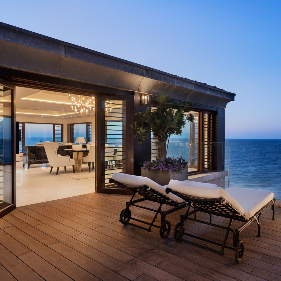 private rooftop deck in presidential suite as it starts to get dark out with views of the ocean
