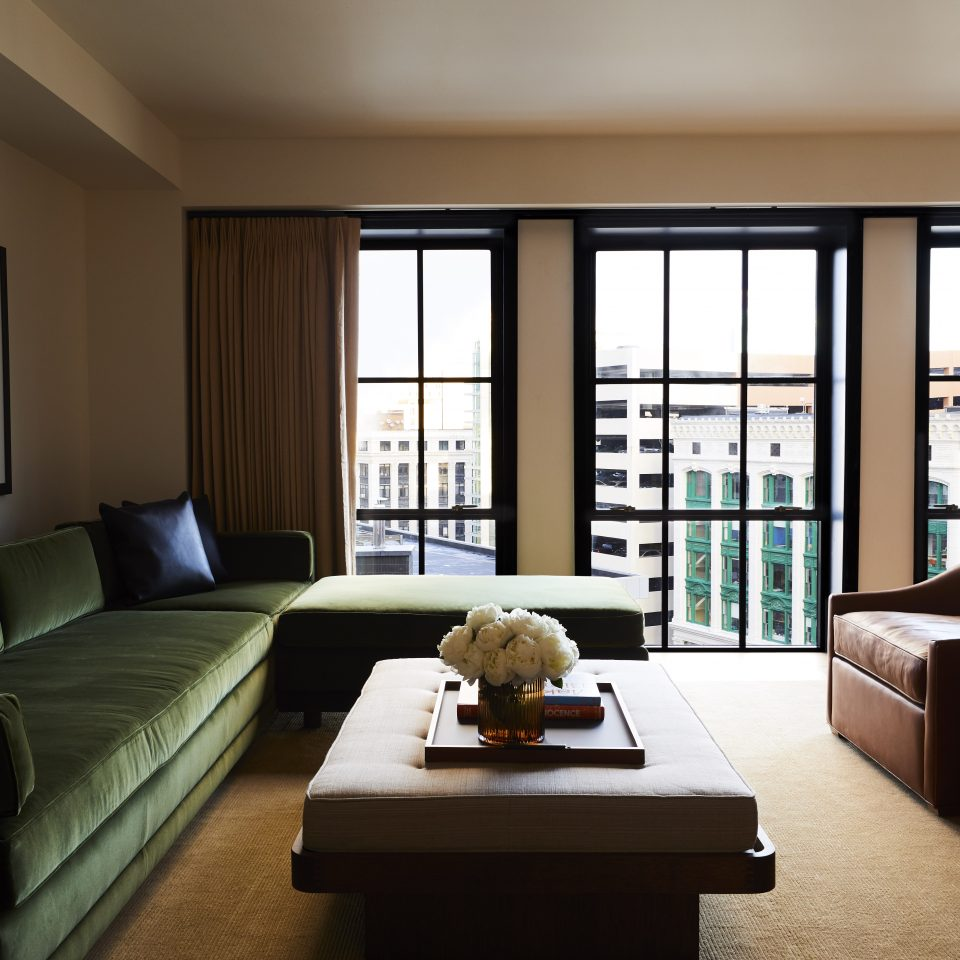 room with large windows, large green velvet couch, and a coffee table with a cushion