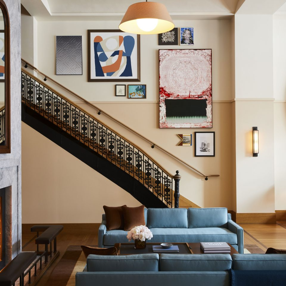 stairs leading down to a room with a fireplace near blue couches and art all over the walls
