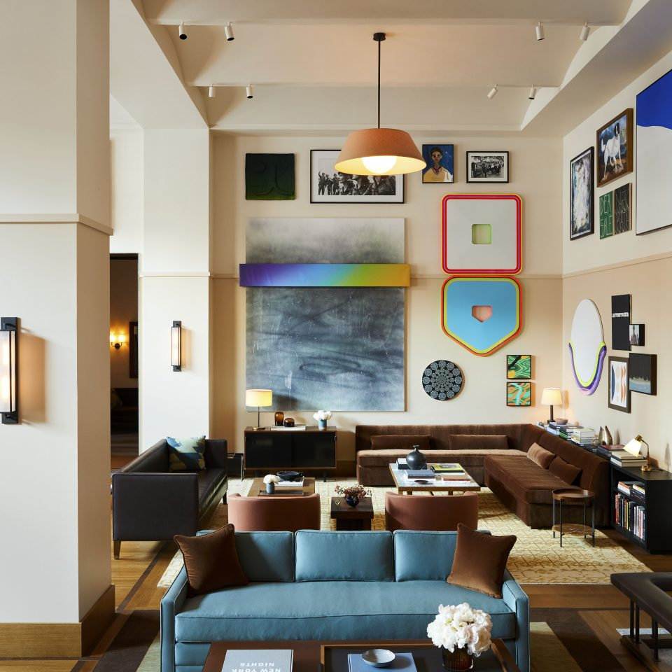room with blue couches and modern art all over the walls
