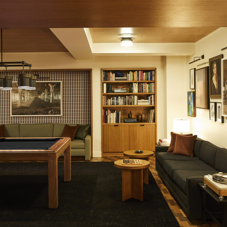 mezzanine room with pool table, short ceiling and bookshelves and couches