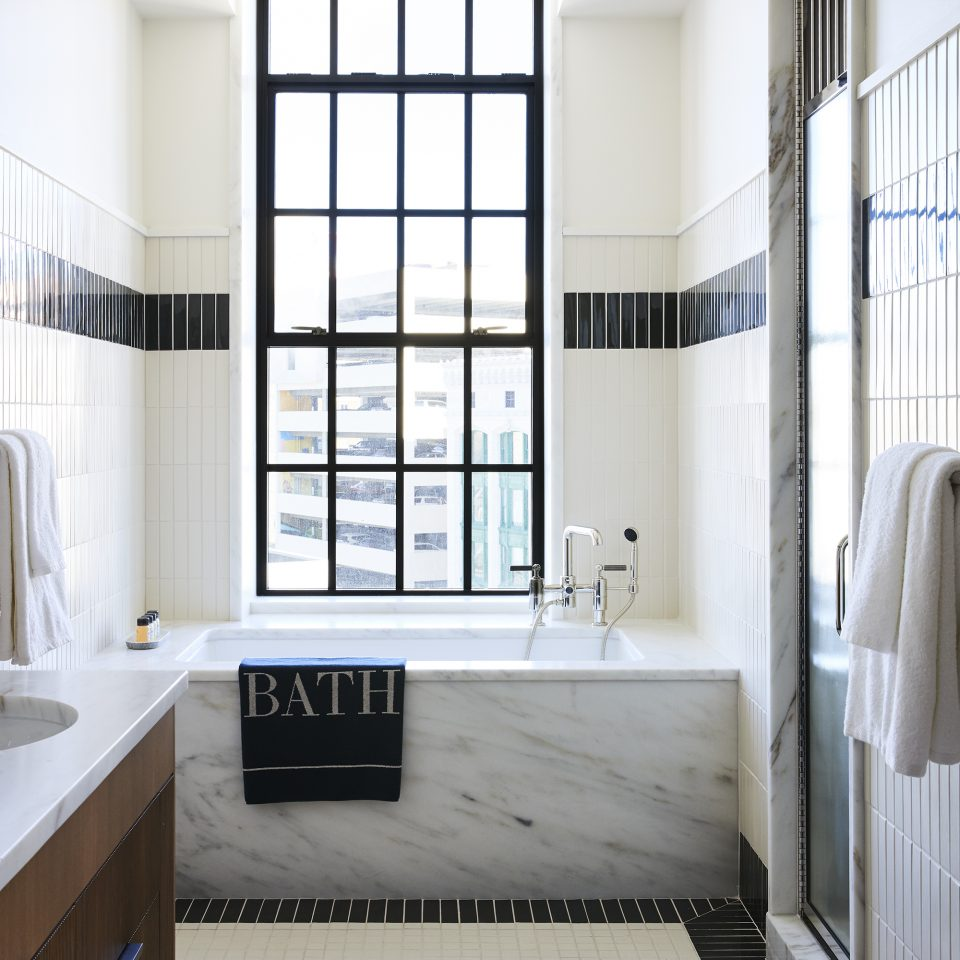 "bathroom with large window and marble bathtub, towel hanging off the side reading ""BATH"""