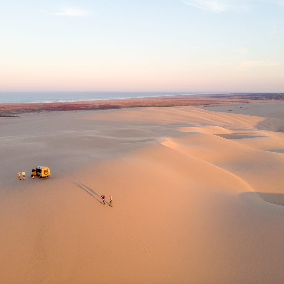 two people walking away from car in the middle of the dessert at sunset