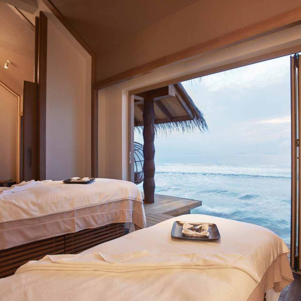 spa over water showing spa beds and a large window of open ocean