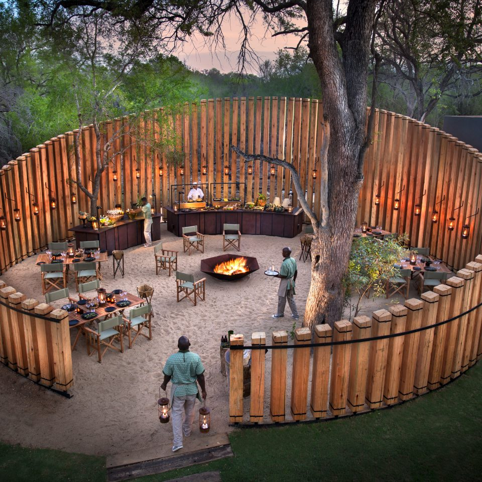 outdoor circular wood pool structure that has an interior of a fire burning and tables for eating with a sandy floor
