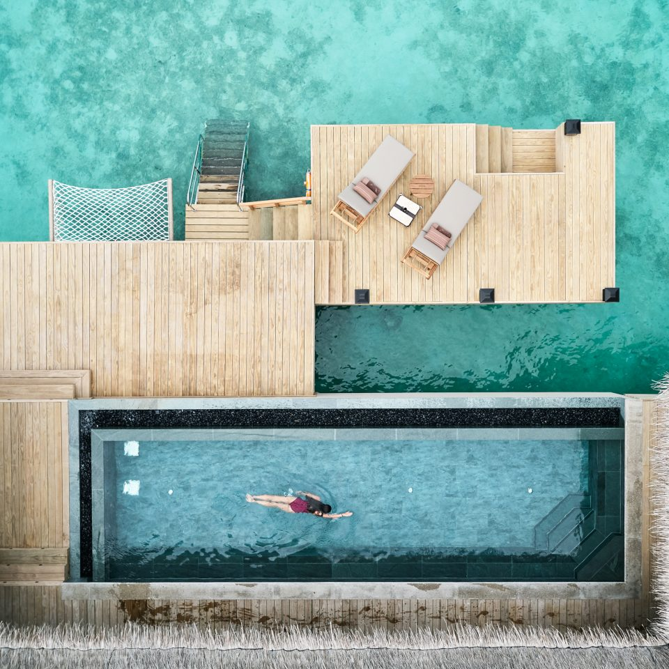 overhead view of woman swimming in villa pool with view of ocean and deck