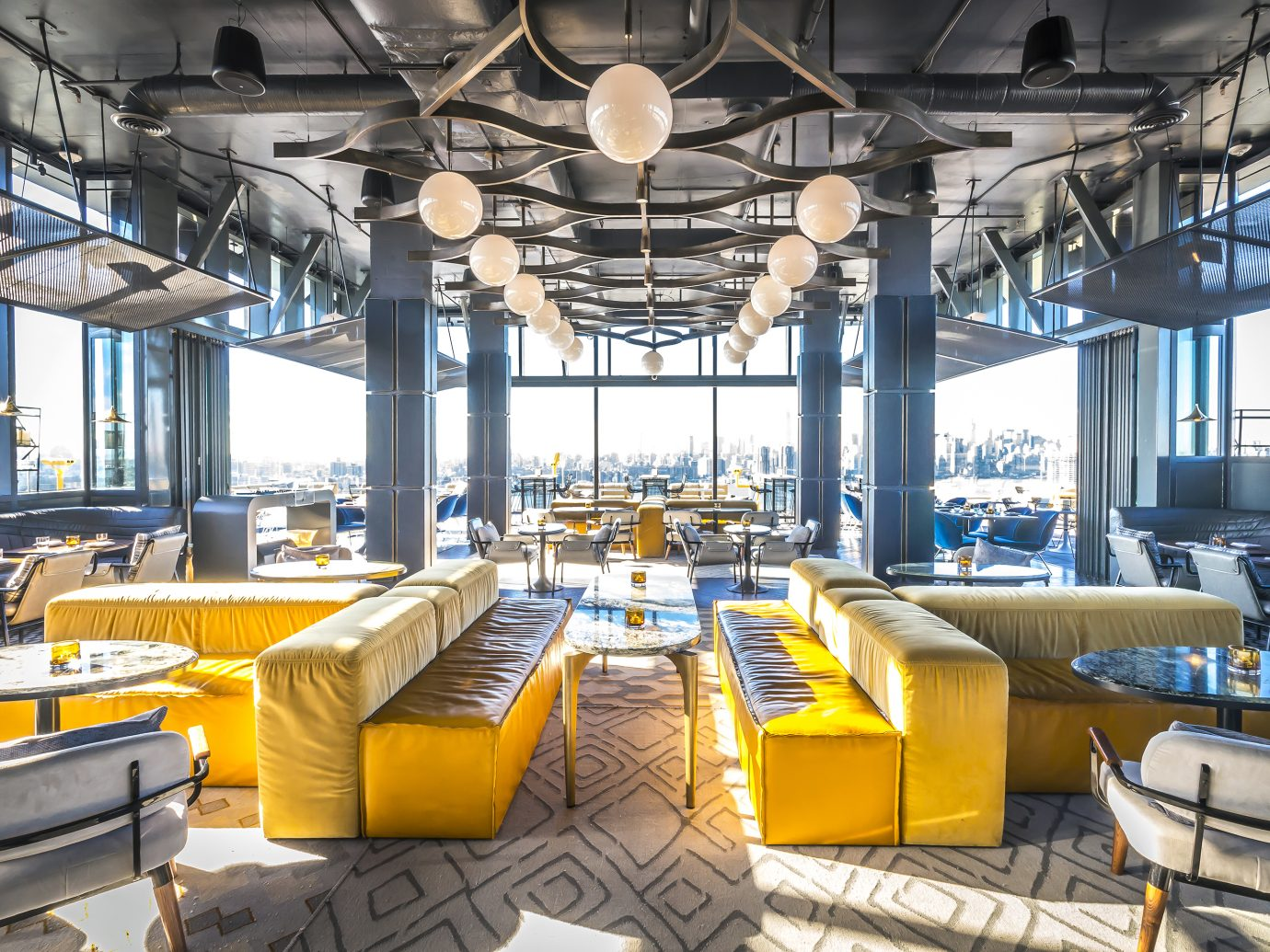 sunny day showing off interior of a bar with bright yellow couches and a very airy space