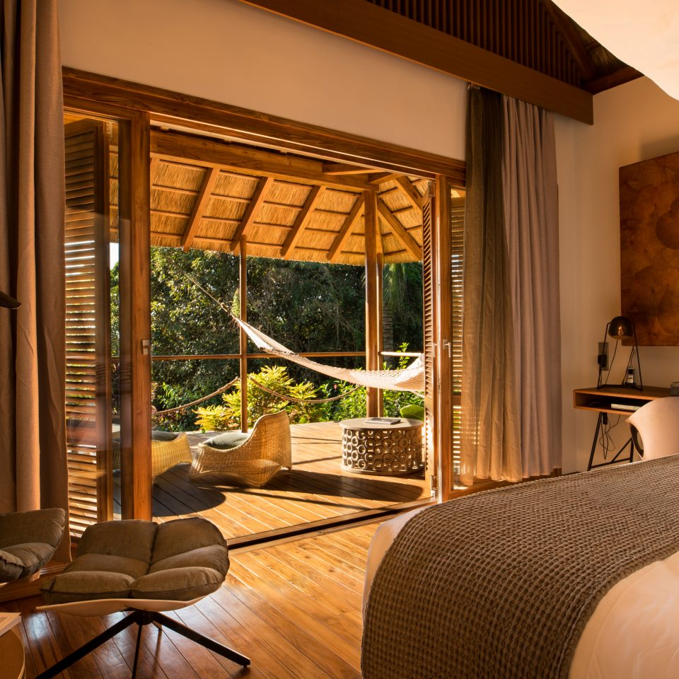 room with a bed with large open doors to balcony space including a hammock
