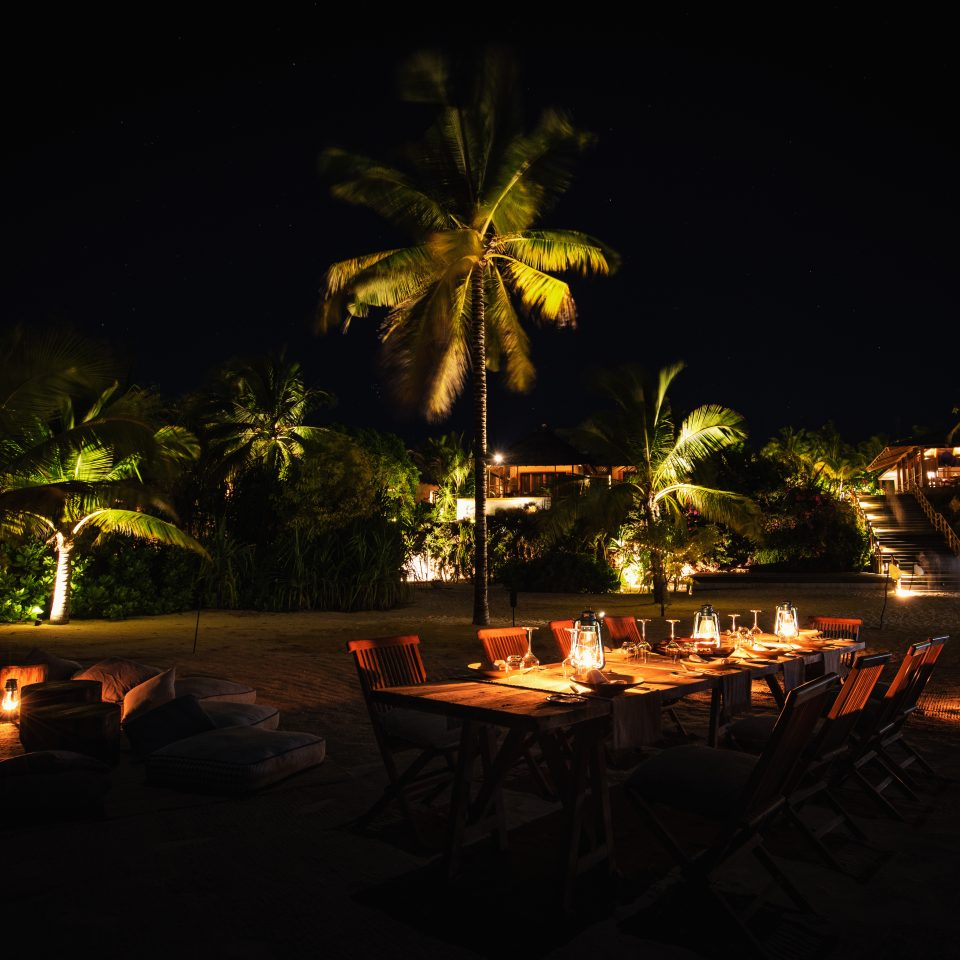 group table set up on the beach in pitch black darkness lit by candles for dinner