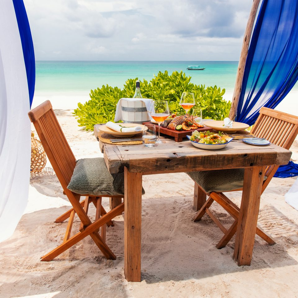 set table on the beach with meal and wine
