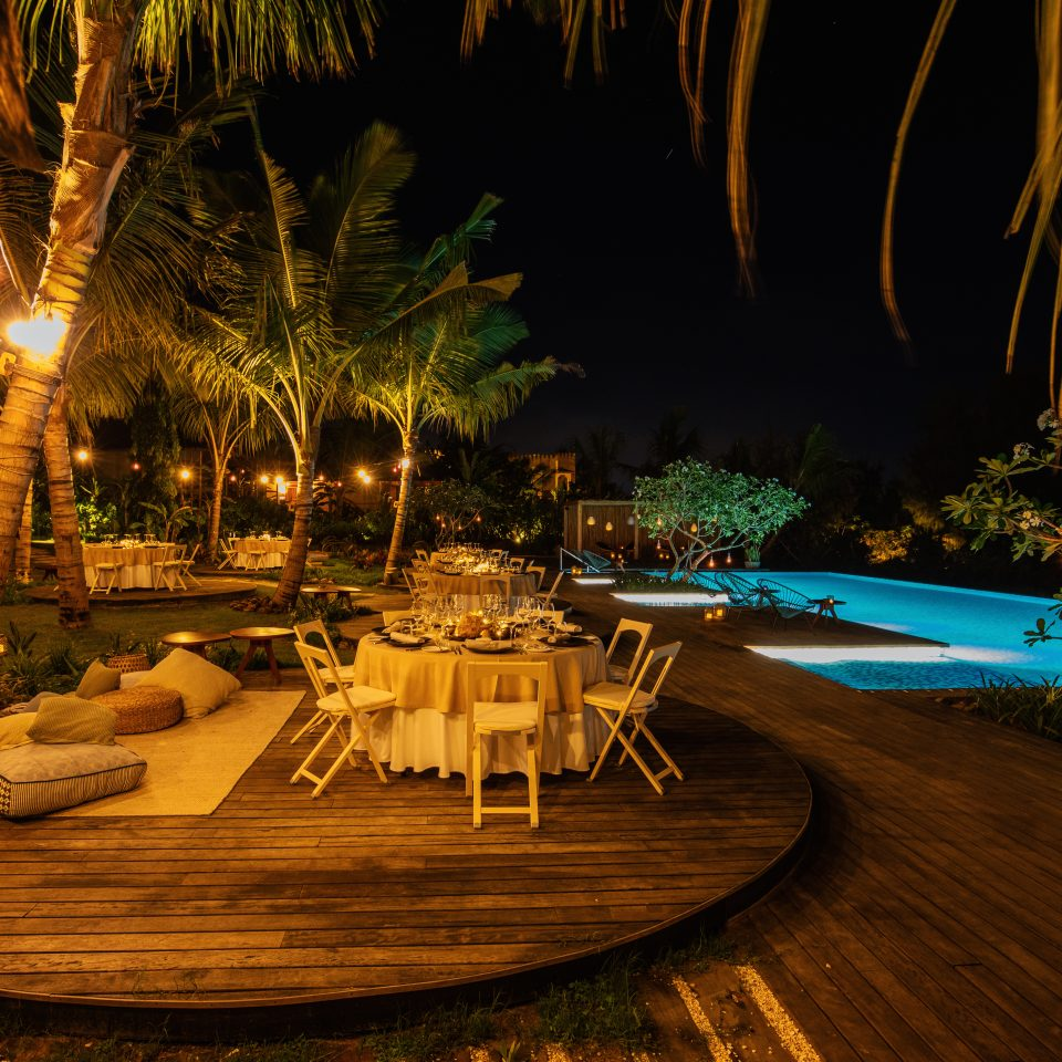 set up table on terrace space with pillow sitting area next to a pool at night