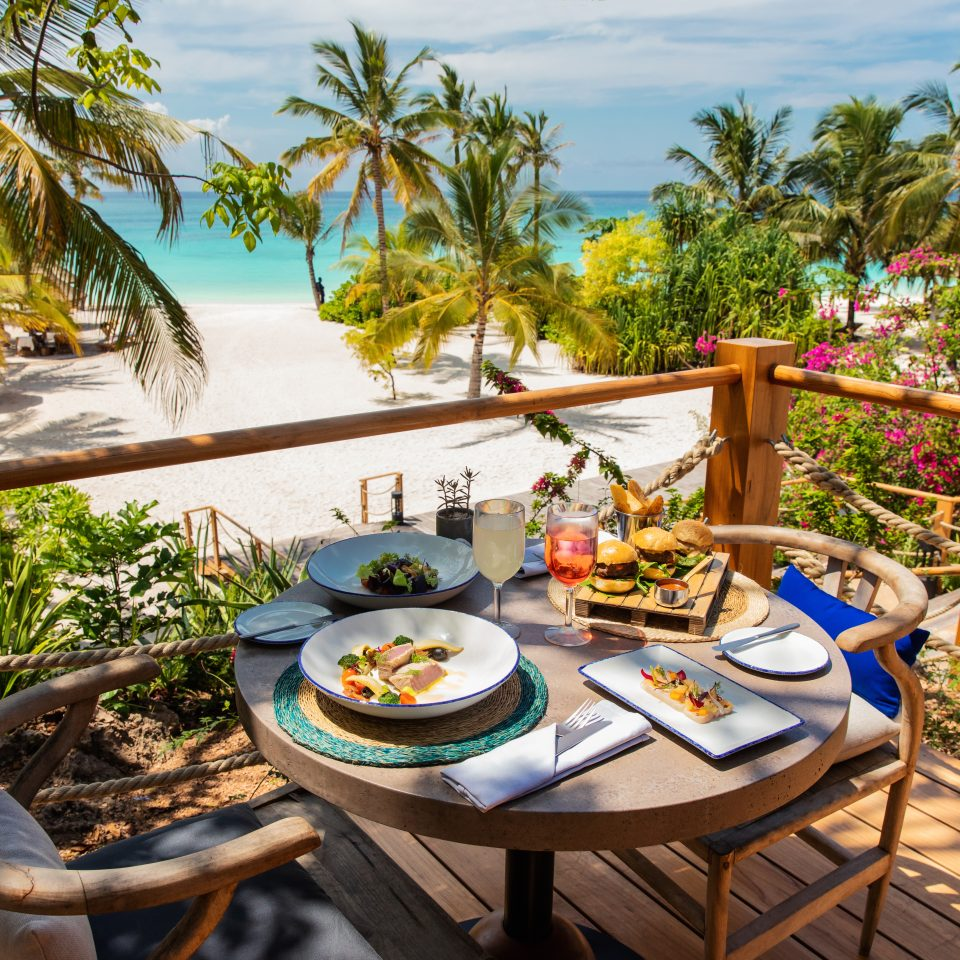 seating and set table full of food overlooking the beach