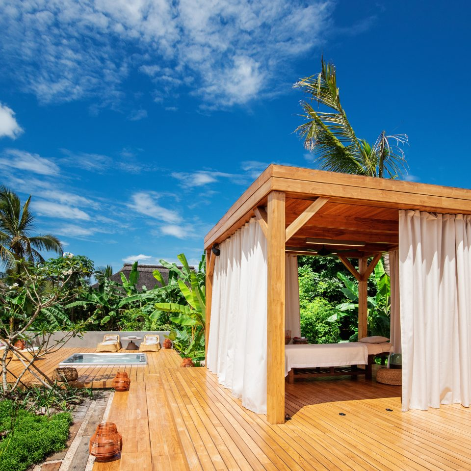 wellness deck on bright sunny day with jacuzzi in the ground and cabanas for healing