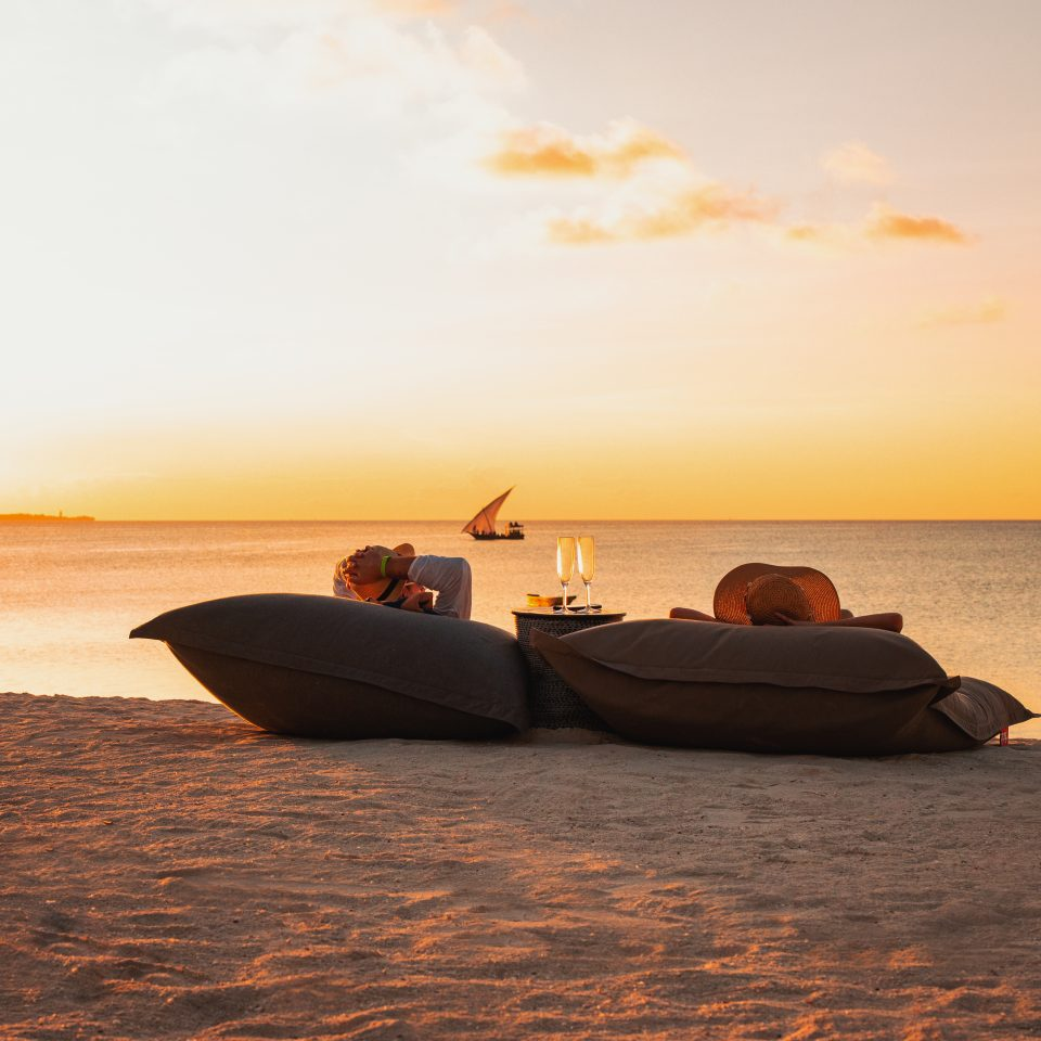 couple resting on large pillows on the beach at sunset with drinks