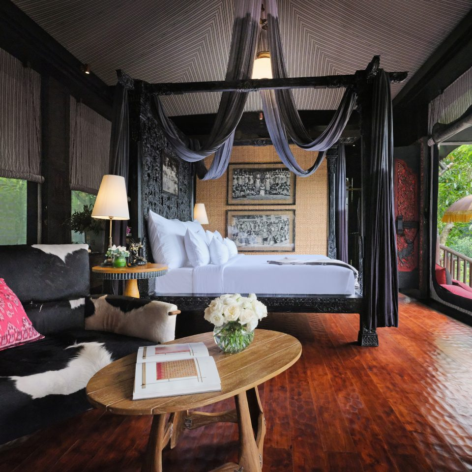 interior of Indonesian themed room with jungle in view from windows, drapery is from ceiling over bed, cow chair