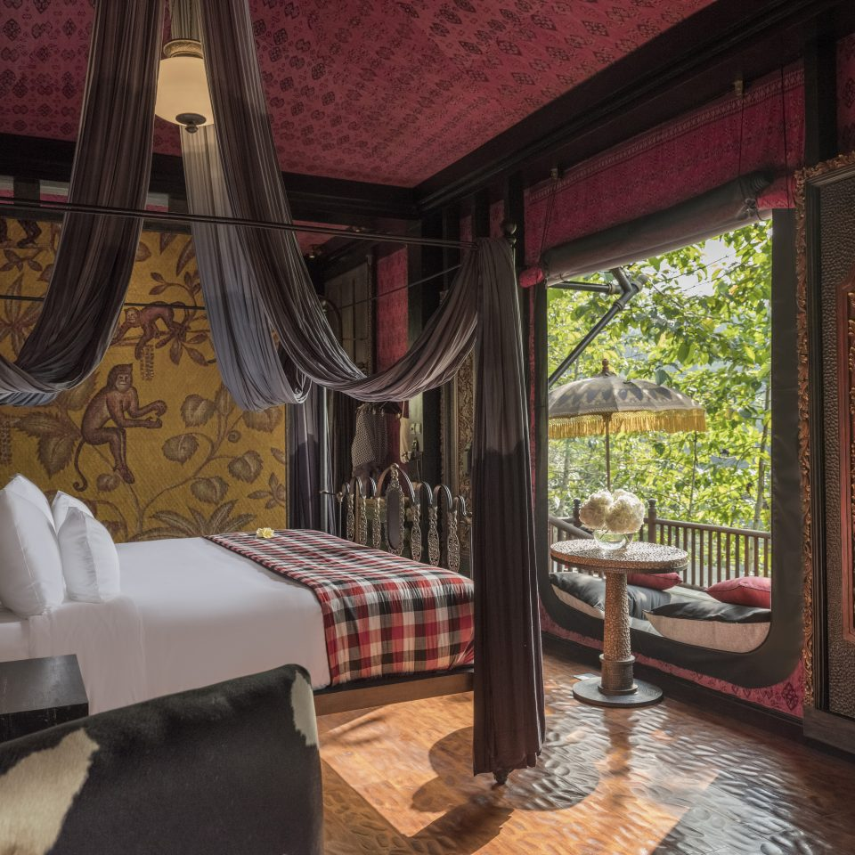 room interior with red walls and ceilings and window views of the jungle
