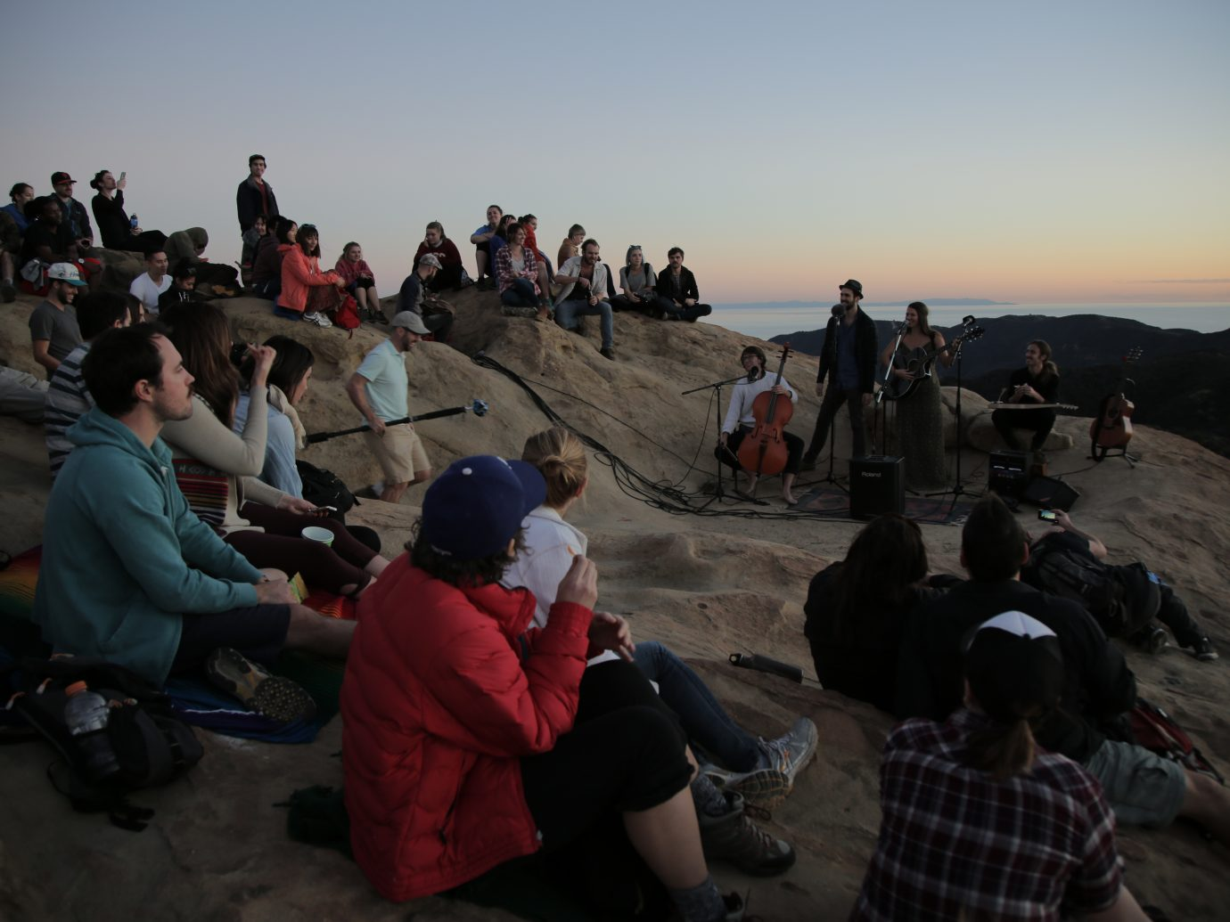 crowd at dusk on large rock watching people perform