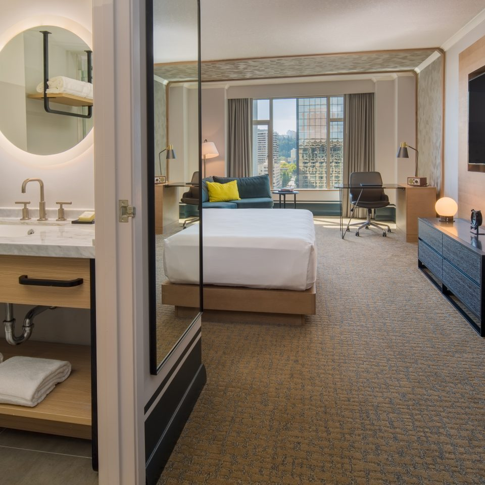 room with bed and mirror with view of bathroom
