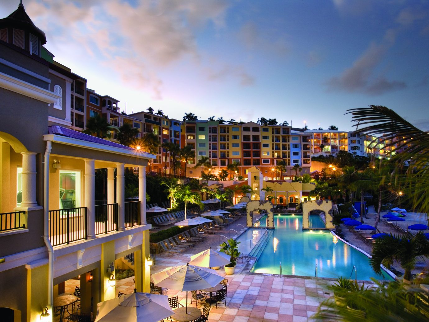 dusk view of colorful resort on water with pool