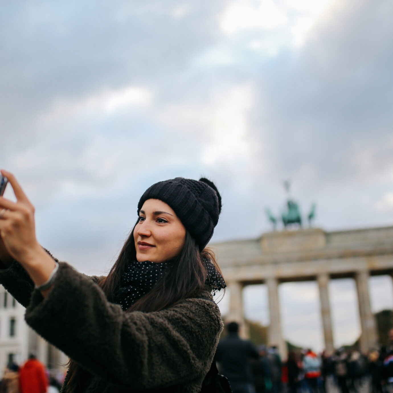 Portrait of a young tourist woman wearing casual clothing, sightseeing, taking selfie images in Berlin Mitte near Brandenburg Gate