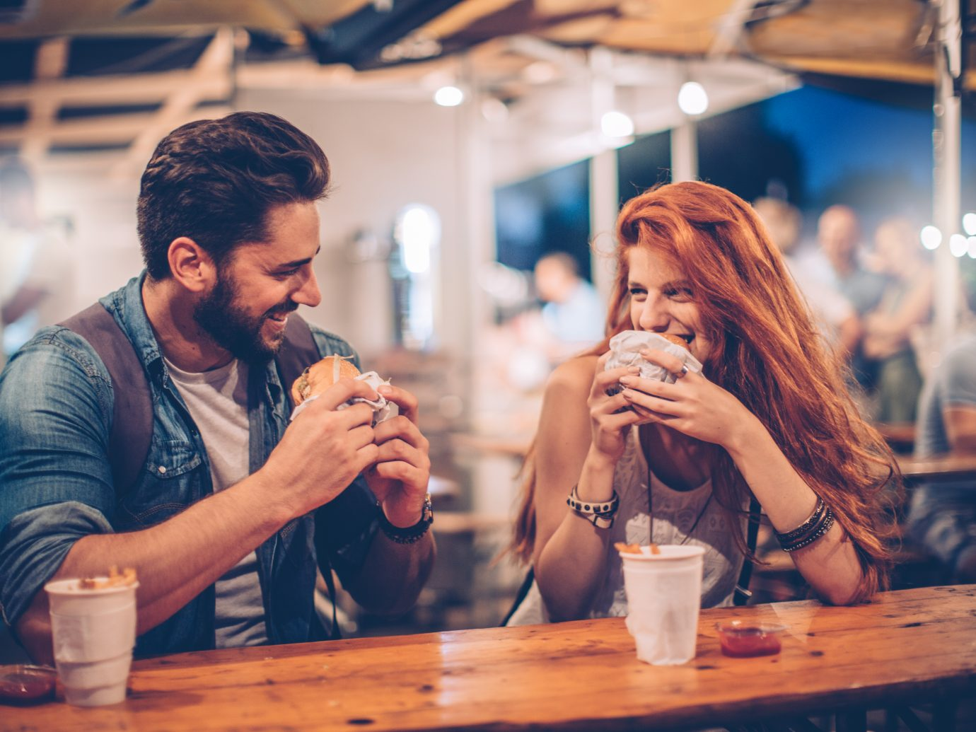 A young couple having snack and drink at an outdoors music festival. Eating burgers with fries and drinking beer.
