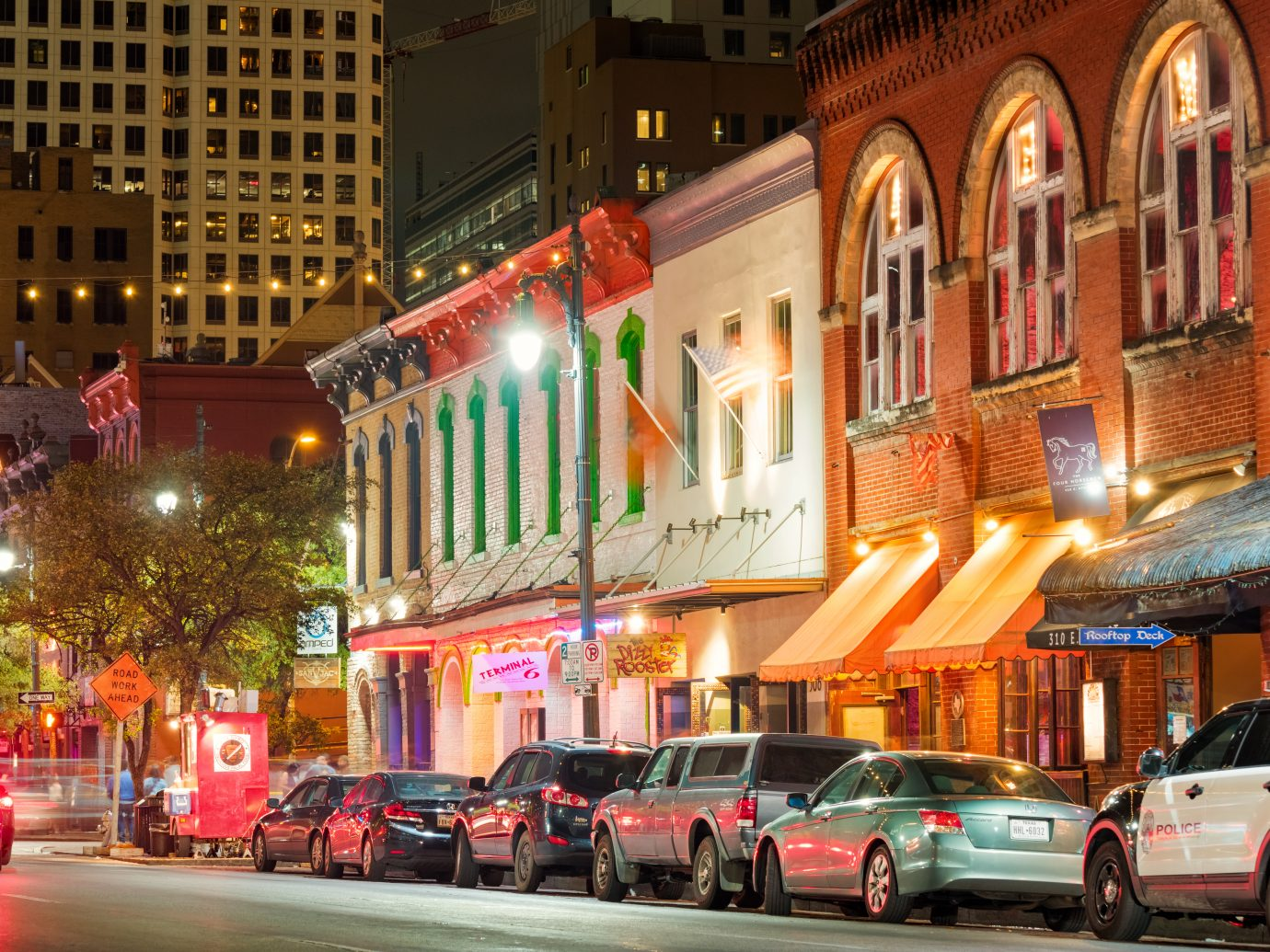 Photo of colorful bars, clubs and businesses at the famous Sixth Street music and entertainment district of downtown Austin, Texas, USA, illuminated at night.