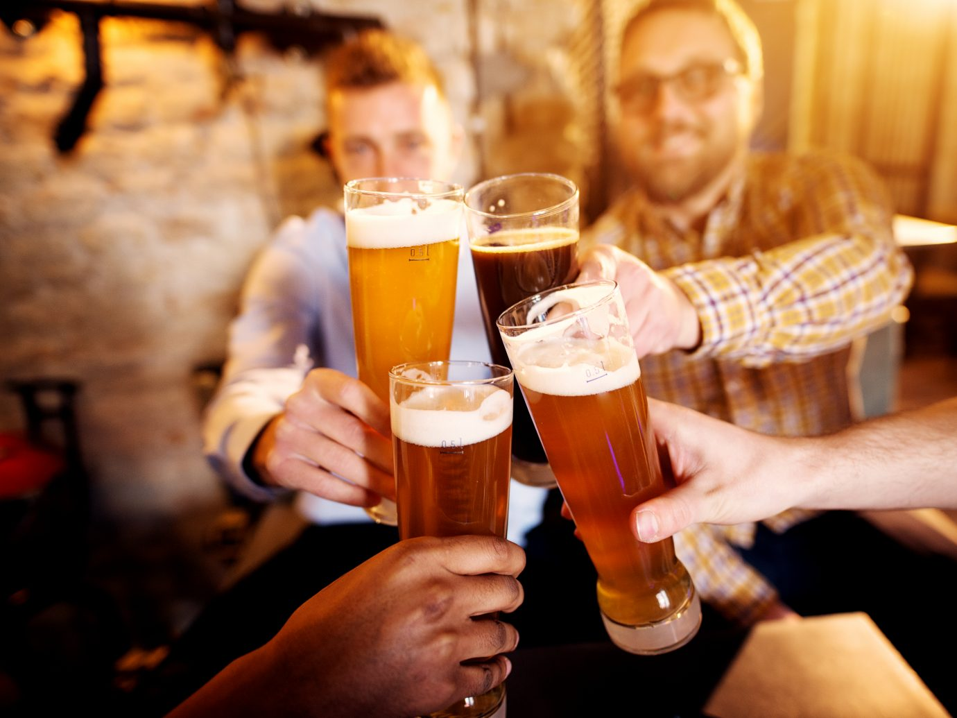 A group of young men clinking glasses with a beer in the sunny pub.