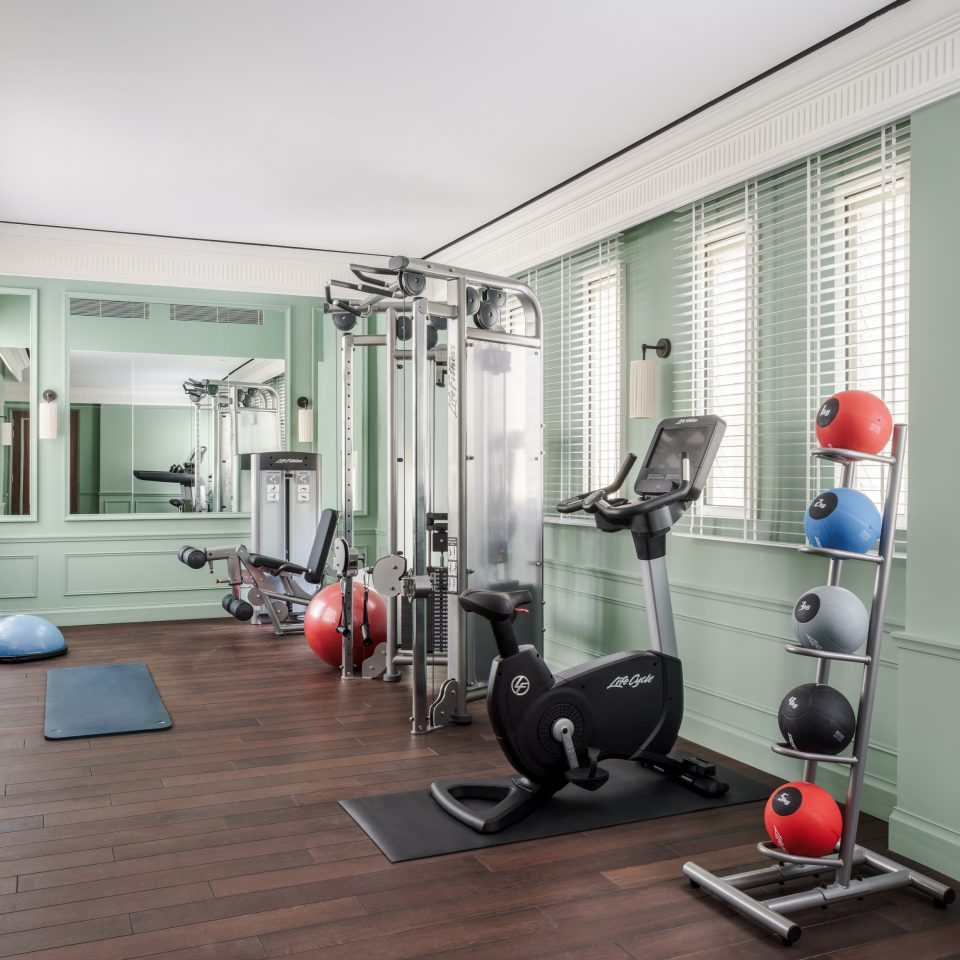 hotel gym with mint green walls and numerous machines
