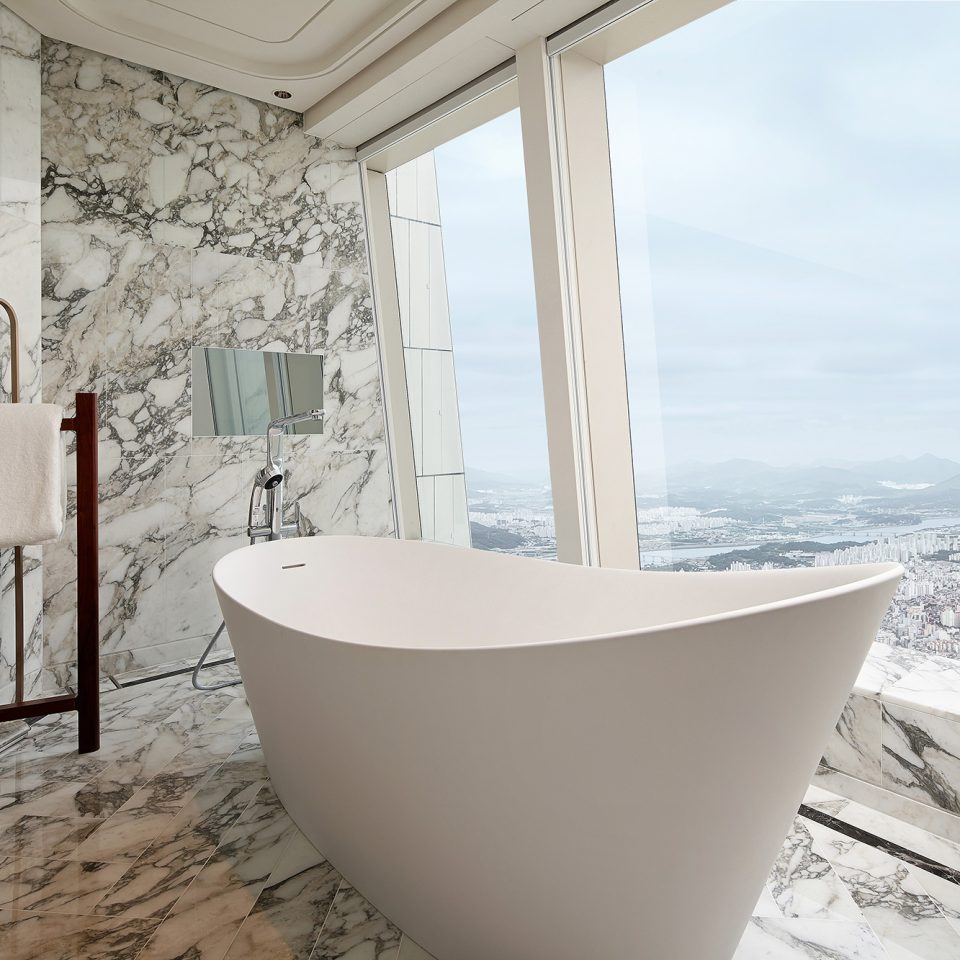 large bathtub in front of window in presidential suite