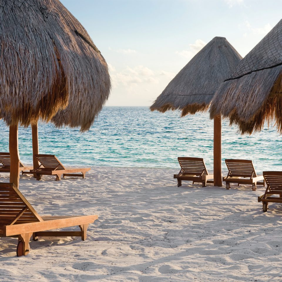 beach with lounge chairs and straw umbrellas