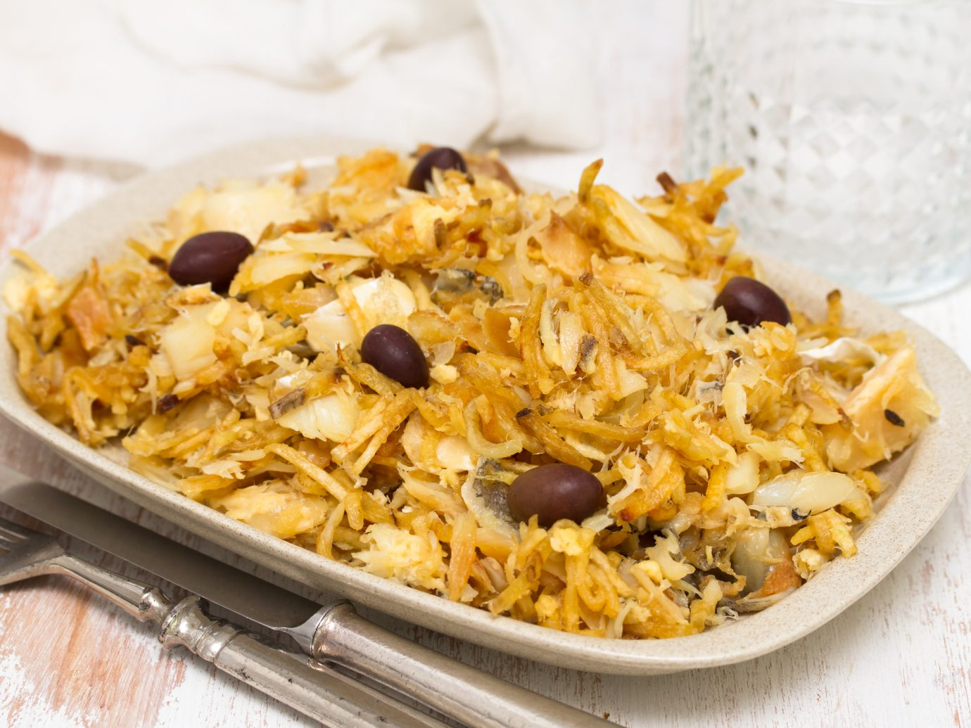 Bacalhau codfish with potato chips and olives on white plate
