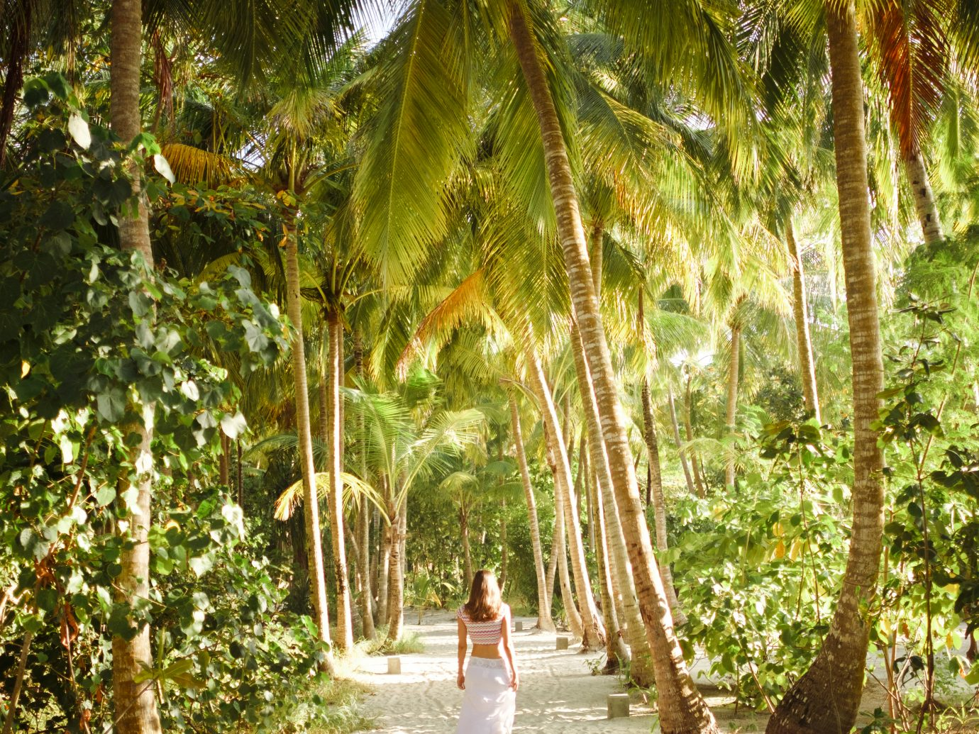 Woman walking down a tropical path at Reethi Faru Resort