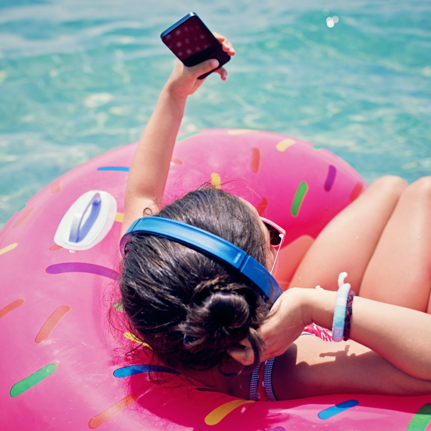 girl floating in the water and listening the music