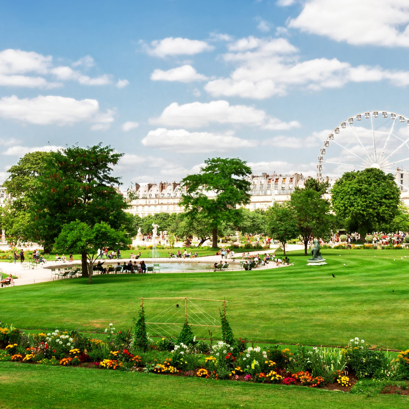 Tuileries garden at summer day, green lawn and blue sky with clouds, Paris France