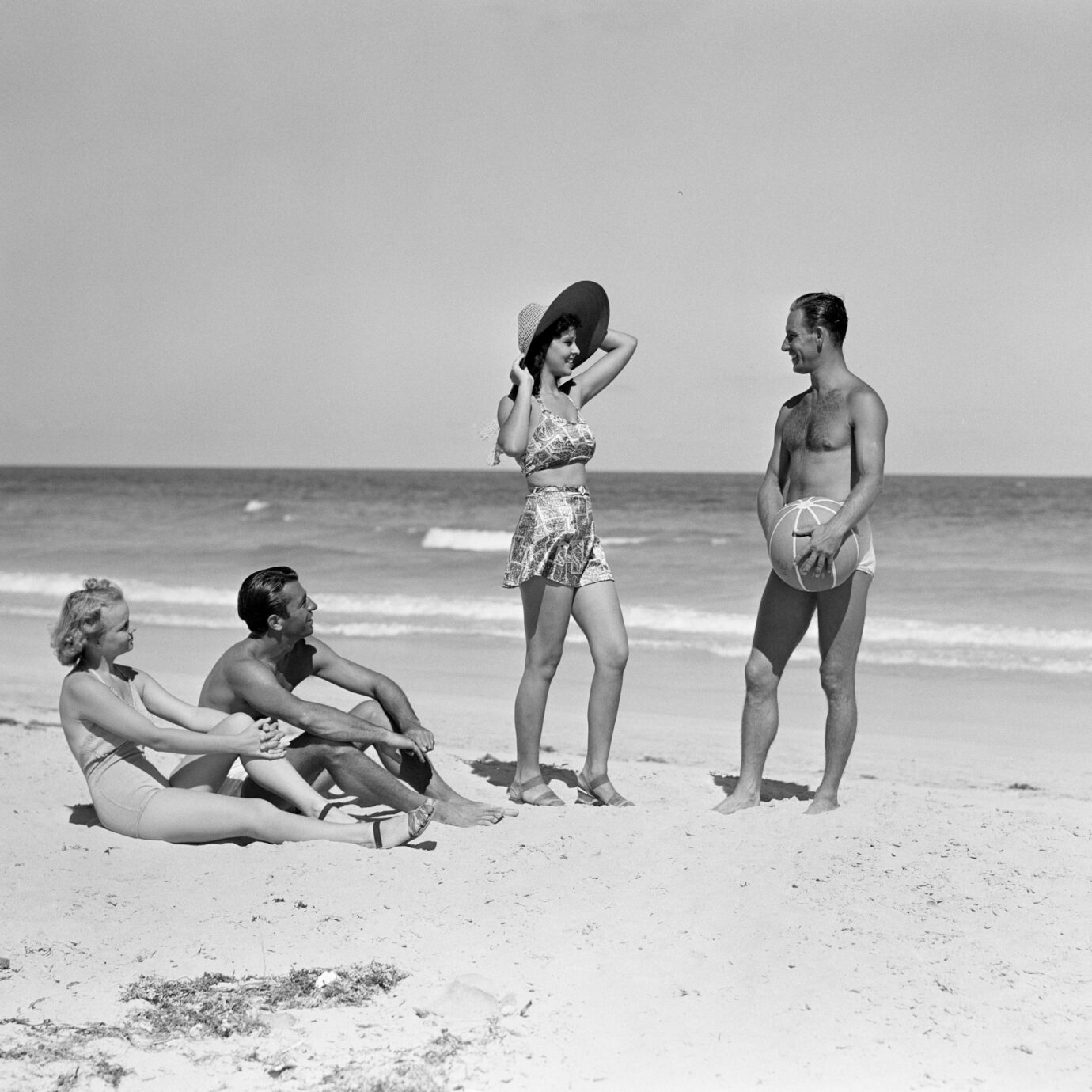 UNITED STATES - CIRCA 1930s: Two couples standing on beach.