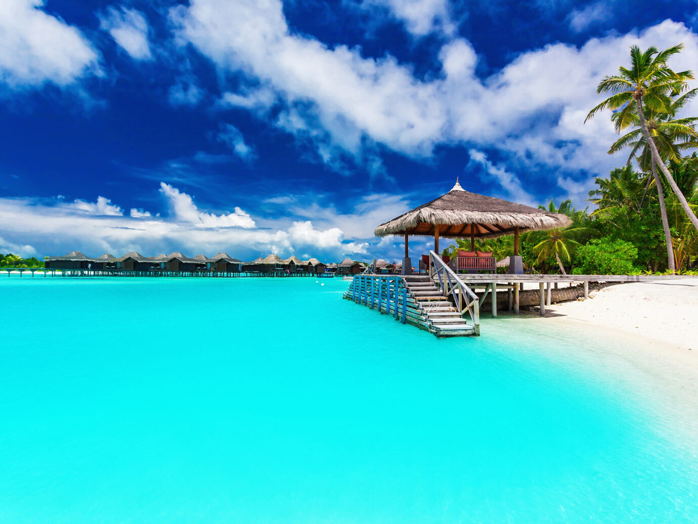 Jetty and palm trees with steps into amazing tropical blue lagoon