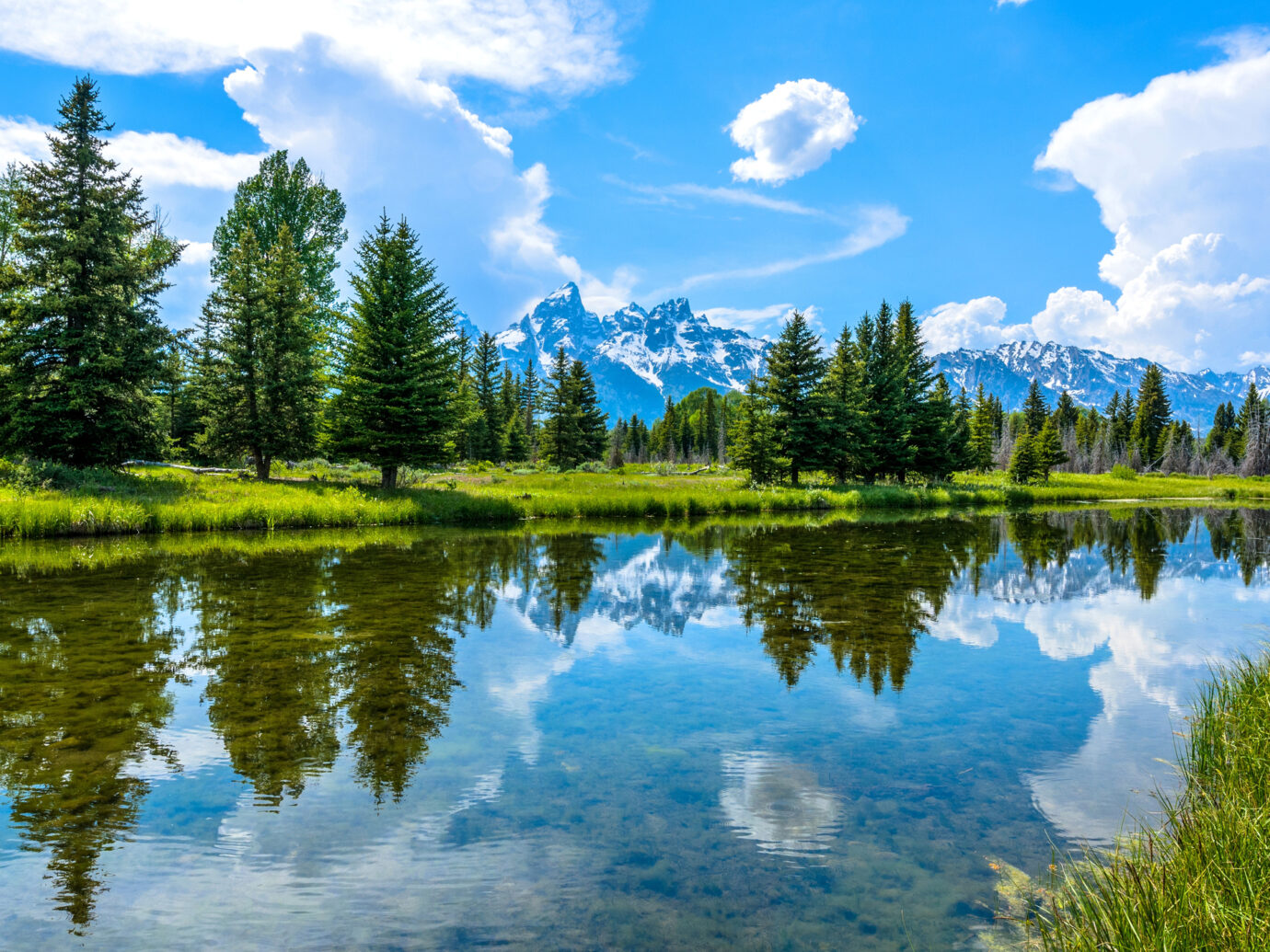 A panoramic spring view of clear and calm Snake River flowing at base of Teton Range in Grand Teton National Park, Wyoming, USA.