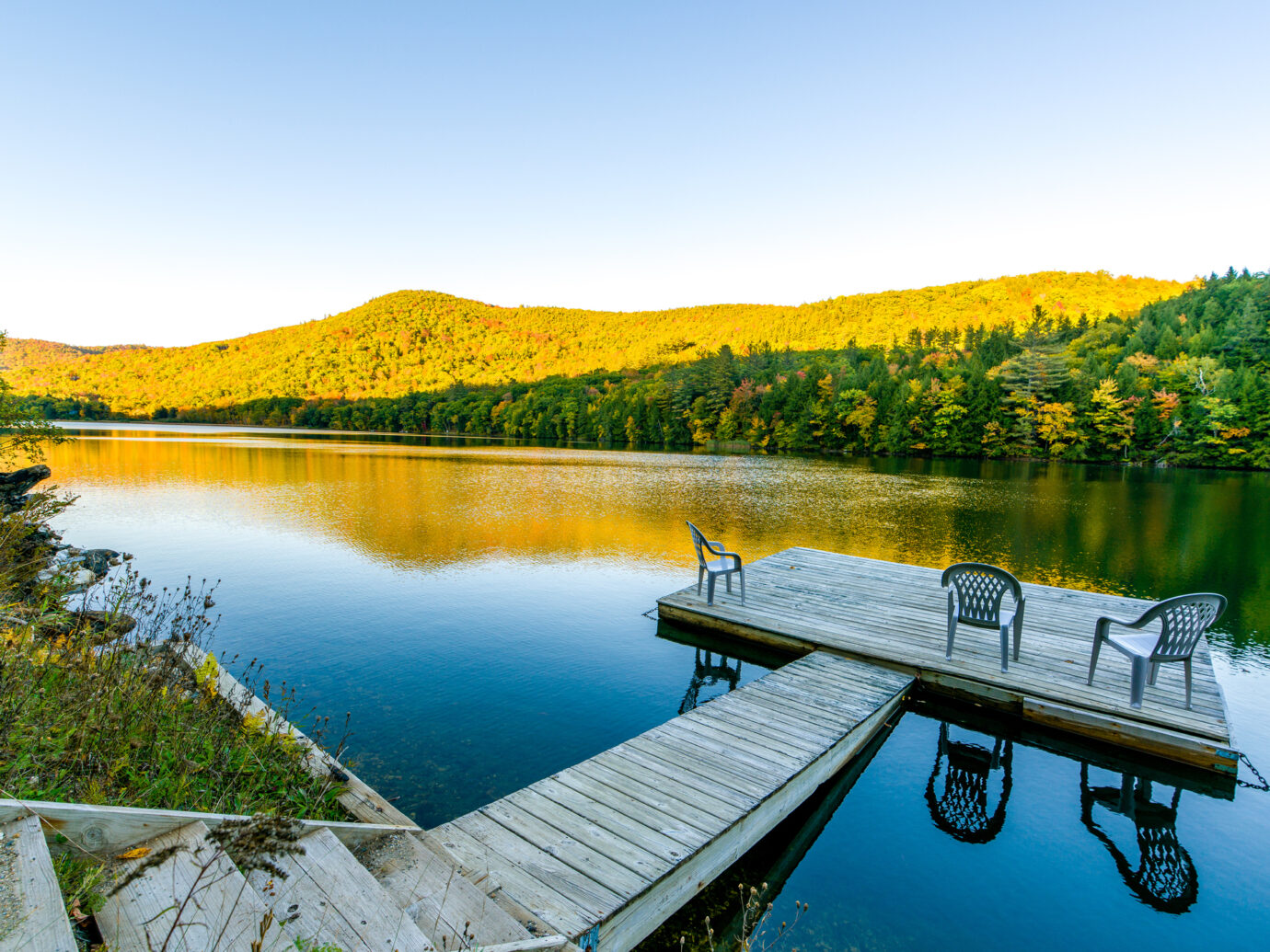 A small deck in the middle of a lake in Vermont. Three chairs are on the deck, inviting people to have a rest