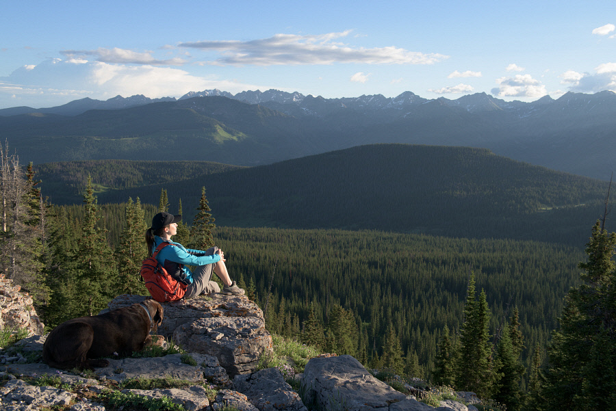 On a clear summer morning, a hiker pauses at the top of Vail Mountain to contemplate the grandeur of a Gore Range sunrise.