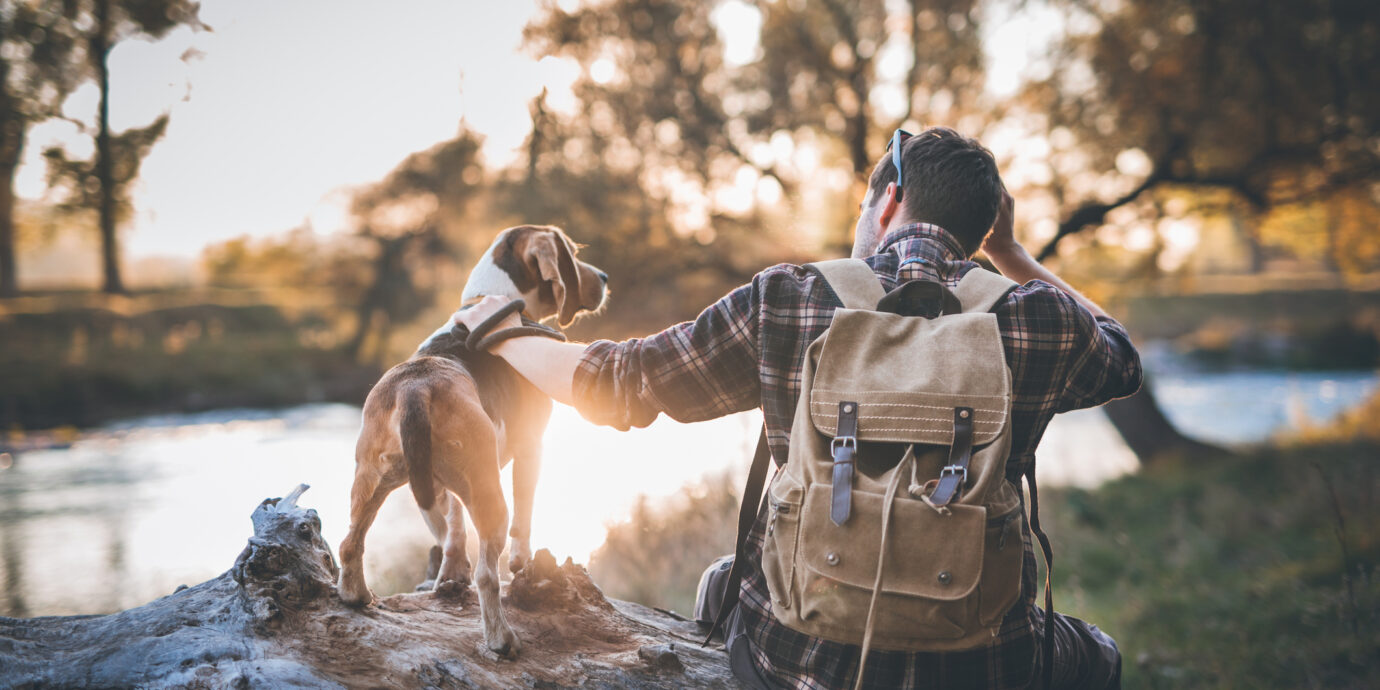 Man hiker and his dog taking a rest from walking, sitting by the river, enjoying the view and sunset