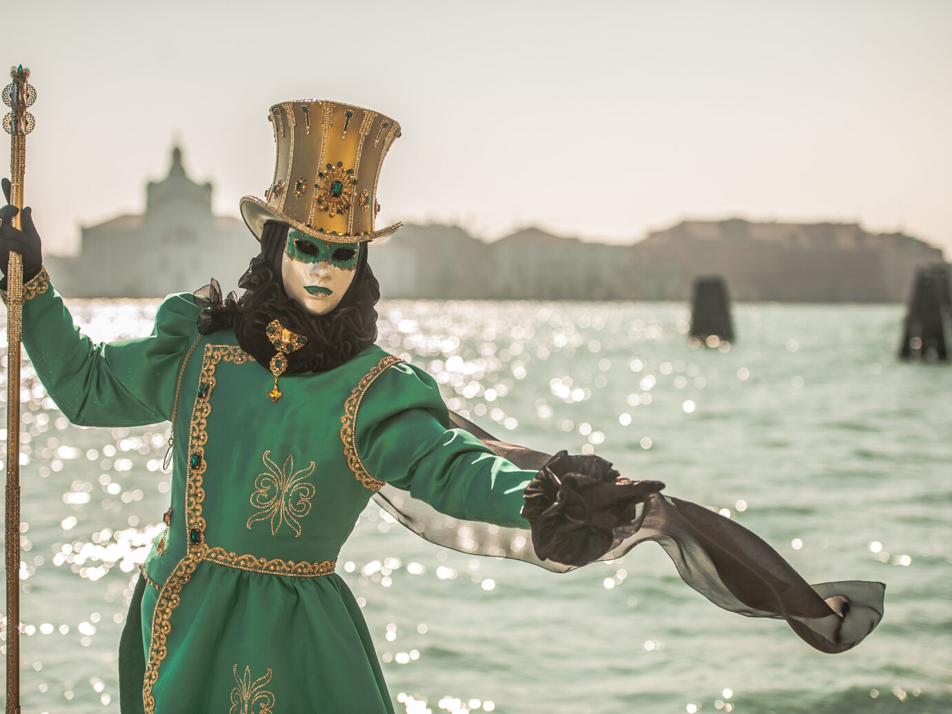 Masked Person in Green Carnival Costume with Golden Hat Posing near Canale Grande, Venice