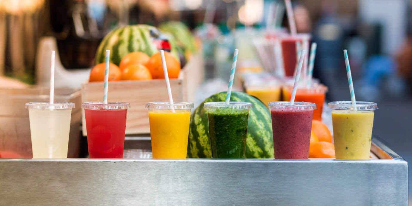 Close up color image depicting freshly made fruit juices and smoothies on display in a row and for sale at a food and drink market in London, UK. Selective focus on the plastic cups containing the fresh smoothies.