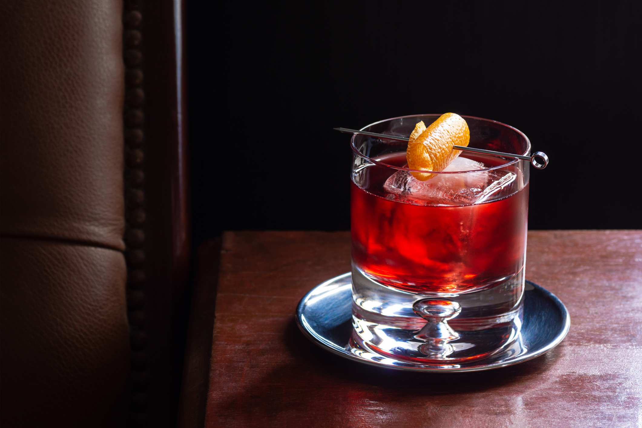 A Negroni cocktail, made from equal parts Campari, gin, and red vermouth in a rocks glass with ice and an orange twist. The drink is in a dark luxurious bar and there is copy space in the black background.