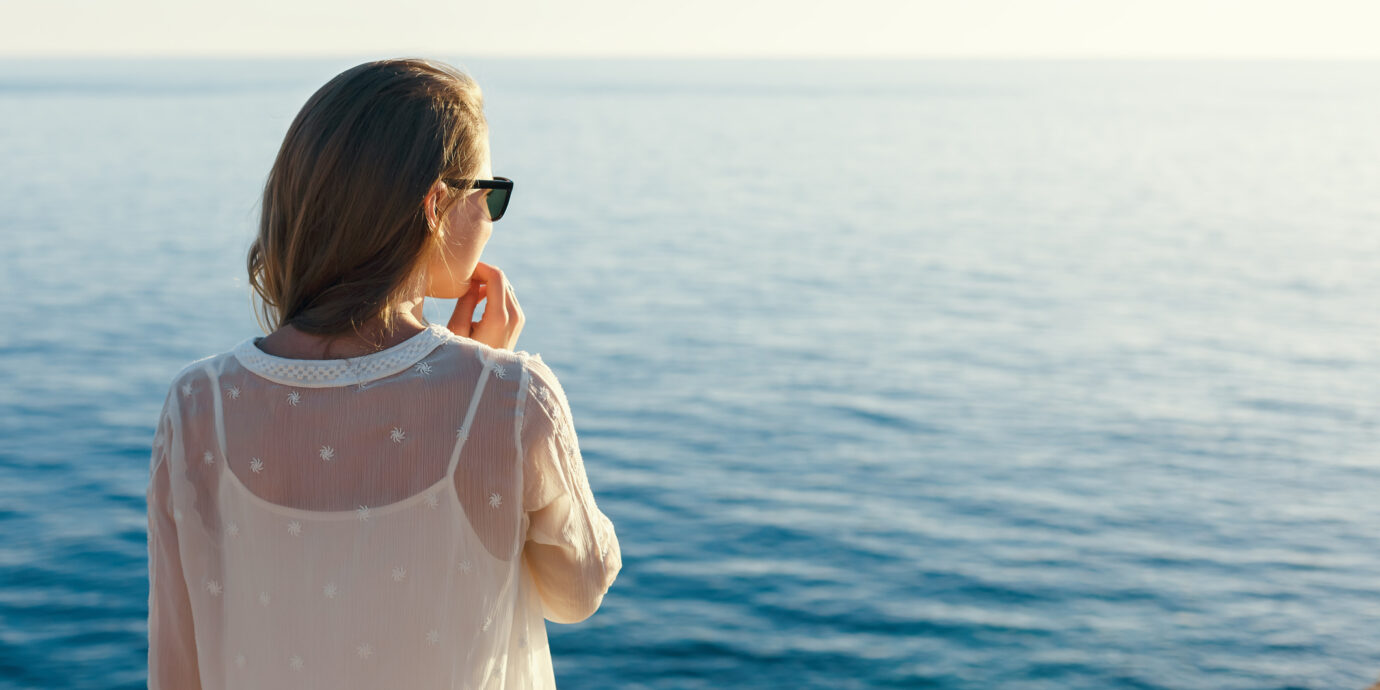 Woman looking at the sea in a white dress