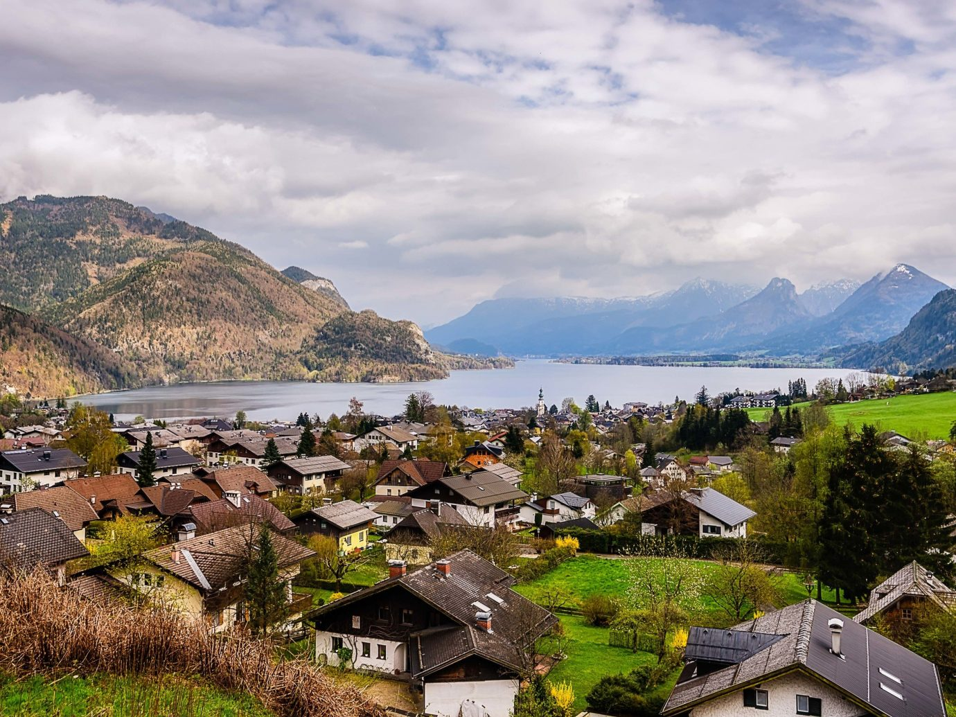 Lakes + Rivers Outdoors + Adventure mountain sky grass outdoor mountain village mountainous landforms Nature mountain range mount scenery highland Village Lake fjord alps valley cloud rural area hill station bank fell tree water landscape canyon tourism hill glacial landform overlooking beautiful hillside lush