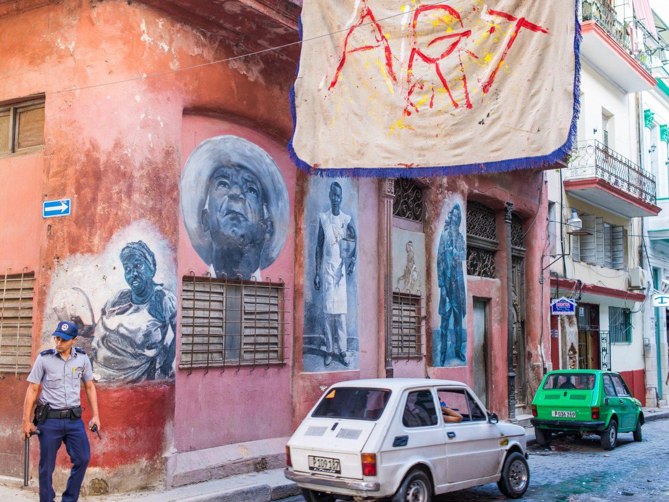 Travel Tips building outdoor color road street urban area parked neighbourhood Town art mural infrastructure graffiti way street art sidewalk