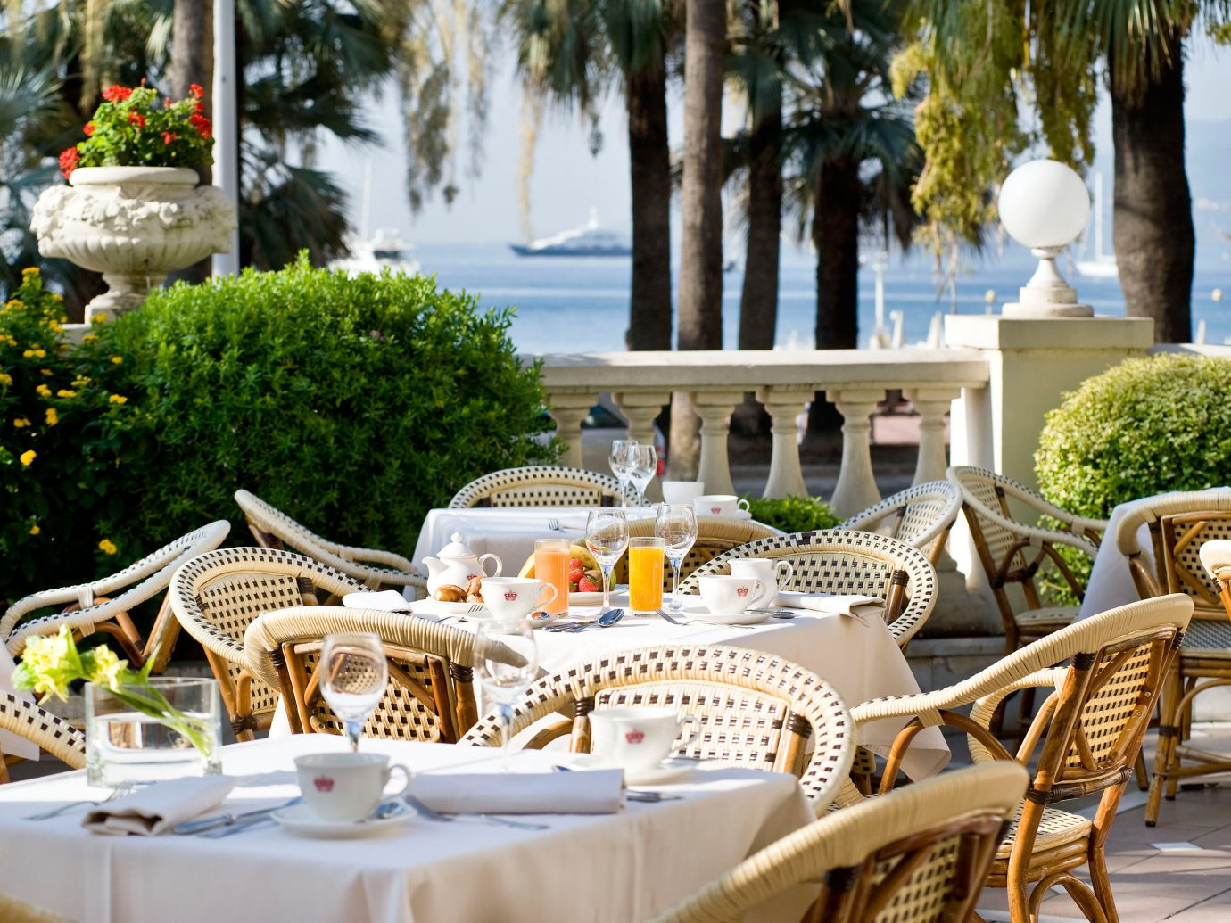 Balcony Dining Drink Eat Hotels Patio Terrace Travel Tips Trip Ideas table tree chair outdoor Picnic meal ceremony wedding estate restaurant backyard outdoor structure dining table