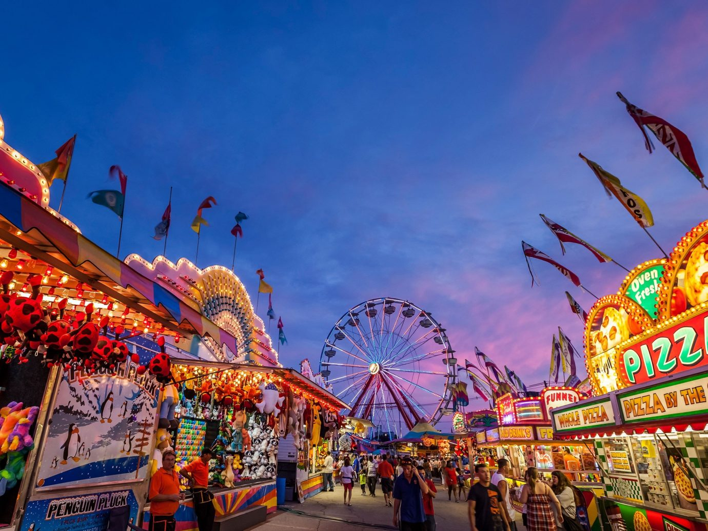 Offbeat sky outdoor ride crowd amusement park fair festival park amusement ride cityscape ferris wheel colorful roller coaster place of worship temple colored